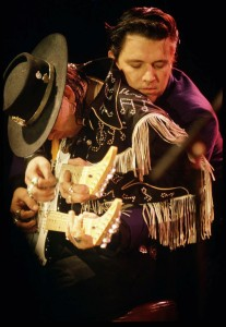 USE ON JUMP IF ROOM Stevie Ray Vaughan, left, and his brother, Jimmie, performing together during recording of a live album at the Austin Opera House. 1986 file photo by Zach Ryall.